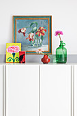 Flowers and pictures on top of tall white sideboard