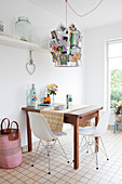 Small wooden breakfast table and classic chairs below metal lampshade decorated with postcards
