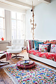 Colourful accessories and classic Eames Lounge Chair in living room of period building