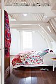 Blick ins weiße Dachgeschosszimmer auf Doppelbett mit bunten Kissen und Steppdecke