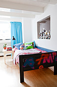 Wooden bed with colourful bed linen, row of trophies and turquoise curtain in boy's bedroom