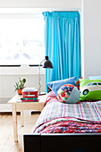 Bed with colourful bed linen, bedside table and turquoise curtain in boy's bedroom