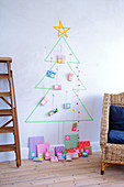 Christmas tree made of masking tape and colorfully wrapped gifts as an advent calendar