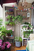 Lush greenery, summery flowers and potting bench on balcony