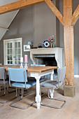 Essitsch mit blauen Freischwingern vor Kamin im Esszimmer mit rustikalen Holzbalken