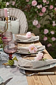 Linen napkins decorated with roses on set table in garden