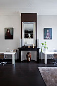 Mirror above the faux fireplace, flanked by white desks and paintings