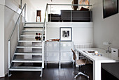 Desk with chair and metal cupboards under metal stairs in loft apartment