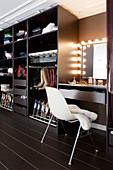 Ankleide mit offenem Schrank in Brauntönen und Schminktisch mit beleuchtetem Spiegel