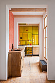 Fitted, solid-wood cupboard in hallway with yellow glass kitchen wall at far end
