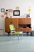 Chair in front of retro sideboard in living room with wooden floor