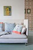 Scatter cushions on pale sofa below portrait on wall