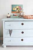 Vintage accessories on old pale blue chest of drawers