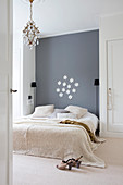 Bed against grey wall between two fitted wardrobes in simple bedroom
