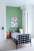 Black metal bed against green wall between two fitted wardrobes in child's bedroom
