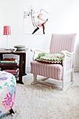 Antiker Sessel mit weiß-rosa gestreiftem Bezug neben dunklem Beistelltisch