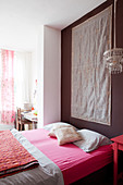 Mattress with a pink sheet in front of a dark wall with a tapestry in the bedroom