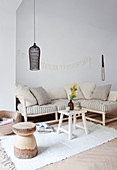 Sitting area with cushions and pillows in natural tones, above a black hanging lamp