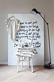 Damenbluse hängt an Leinwand mit Botschaft, davor Stehlampe und Stuhl