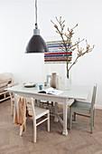 Schwarze Pendelleuchte über Esstisch mit Stühlen, Zweig in Vase, dahinter Wandbehang mit Botschaft