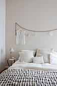 Doppelbett mit Kissen, Damenbluse an Holzperlenkette hängend im Schlafzimmer in Beigetönen