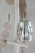Lantern made from slashed tin can and garland of capiz shells