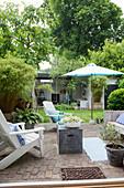 Deckchairs on paved terrace in summery garden