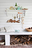 Maritime ornaments on shelf on board wall above bench with firewood stored below
