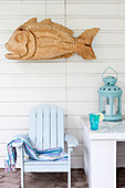 Fisch-Skulptur aus Holz an der Bretterwand über hellblauen Deckchair