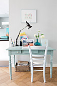 White chair at pale blue desk with anglepoise lamp