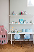 Two pale blue children's chairs at desk below two floating shelves