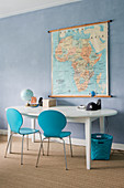 Two blue chairs at oval table below map on blue wall