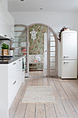 Retro fridge, wooden floor and arched lattice door in white kitchen