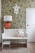 Bench and coral-pink lamp below cuckoo clock on vintage-style wallpaper