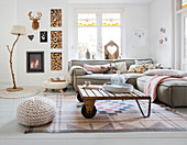 Sofa set, coffee table and fireplace in bright living room with knitted and crocheted accessories