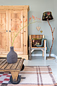 Branch of berries in demijohn with felted cover on rustic wooden table, wardrobe, wooden chair and standard lamp in living room