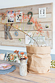 Branch of berries in glass vase in brown paper bag in front of pinboard made from wooden planks