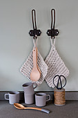 Knitted pot holders and wooden spoons hung from black hooks above mugs, spoon and reel of twine
