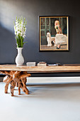 Rustic table with legs made from polished tree roots below painting on grey wall
