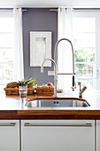 Sink with flexible tap in kitchen with wooden worksurface