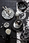 Black and white dishes on a black table with black and white wallpaper strips