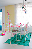 Colourful accessories in white dining room and Christmas tree made from wooden slats