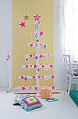 Christmas tree made from wooden slats decorated with pink stars against yellow wallpaper