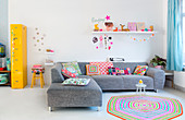Grey sofa on white floor in living room with colourful accesories