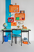 Desk against wall with blue stripe and below colourful plastic crates used as shelf modules