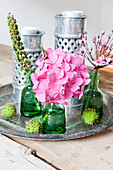 Flowers in green bottles and metal candle lanterns on vintage tray
