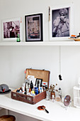 Vintage suitcase of cosmetics on dressing table below photographs on shelf