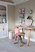 Alter Drehstuhl vor rustikalem Schreibtisch aus Holz vor Bretterwand
