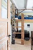 Hochbett mit rustikaler Leiter aus recyceltem Holz im Kinderzimmer