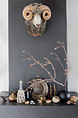Faux hunting trophy on chimney breast and ornaments on mantelpiece